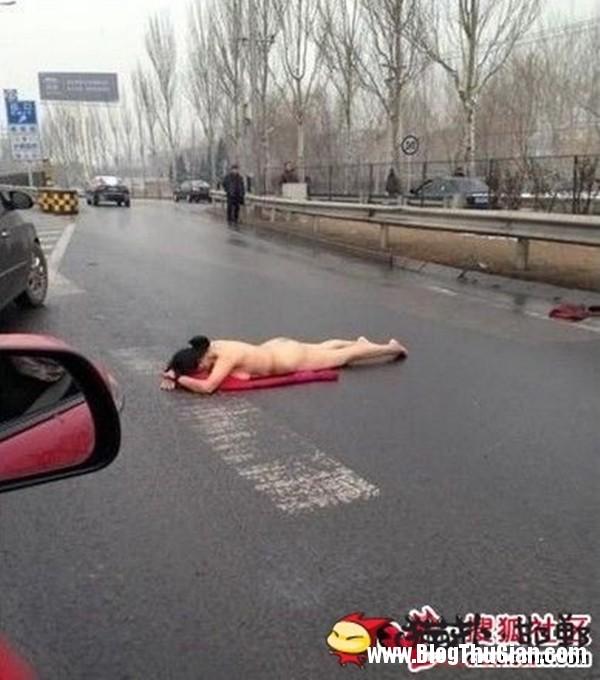 nguoi phu nu khoa than nam up mat xuong duong giua gia lanh Người phụ nữ khỏa thân nằm úp mặt xuống đường